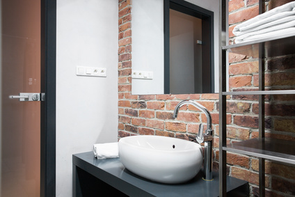 Small modern bathroom with brick wall in home