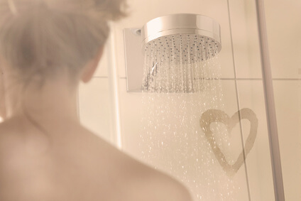 Woman in a shower cubicle with heart shape drawn on the screen