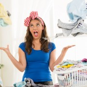 Depressed young housewife with basket laundry for ironing