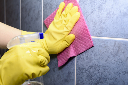 Scrubbing tiles in the kitchen with yellow gloves
