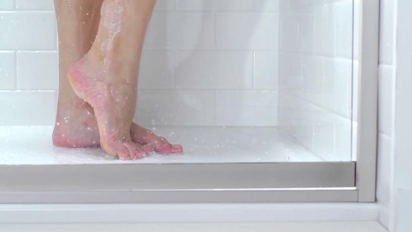 Piedi femminili su piatto doccia