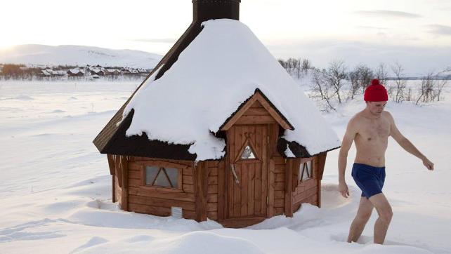 Uomo in mutande nella neve fuori da una sauna