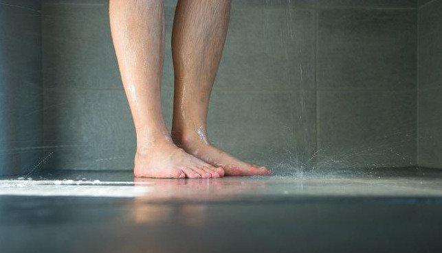 Piedi di persona che fa la doccia