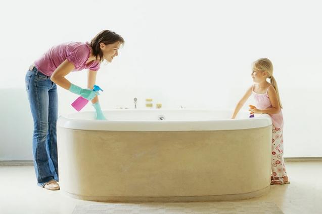 Madre e figlia che puliscono la vasca da bagno